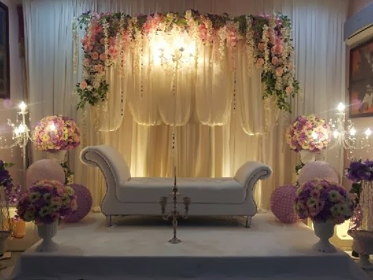 white pelamin couch and pink flowers