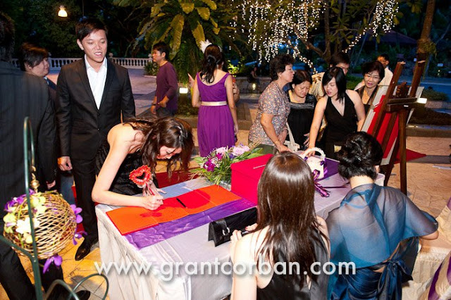 signing their names on wedding signature book