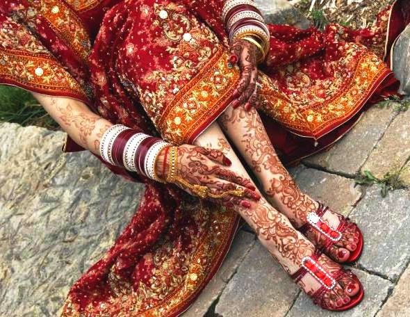 complicated paterns drawn on hands feet of bride